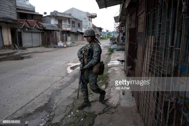 Philippine Marines take positions to clear a street from armed militants on May 28 2017 in Marawi city southern Philippines Filipino authorities...
