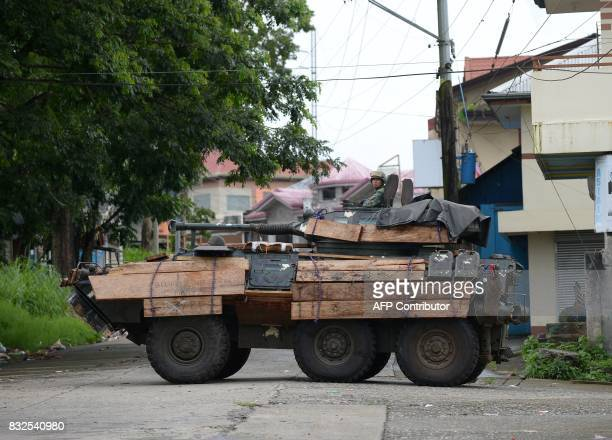 A Philippine marines V300 lightarmored vehicle with wooden planks to protect it from rocketpropelled grenade from Muslim militants crosses a deserted...