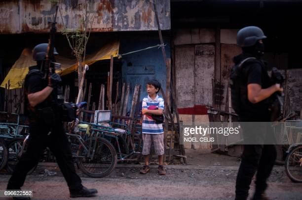 TOPSHOT Philippine members of Special Weapons and Tactics patrol a neighborhood where evacuees from Marawi City are temporarily living in Iligan City...