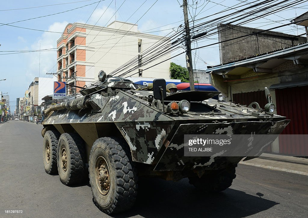 A Philippine military armored personnel carrier arrives near the site of the stand-off between government forces and the remnants of Muslim rebels in Zamboanga on the southern Philippine island of Mindanao on September 20, 2013. Philippine security forces killed eight Muslim rebels on September 20 as they hunted the remnants of a guerrilla force hiding in homes of a major city and believed to be holding hostages.
