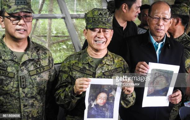 Philippine military chief General Eduardo Ano holds an image of Islamic militant leader Isnilon Hapilon next to Defence Secretary Delfin Lorenzana...