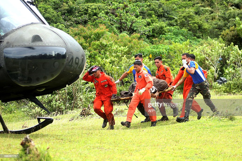 Philippine military personnel carry a makeshift stretcher containing the dead body of one of the foreigners killed when Mayon volcano spewed ash and hail of rocks May 7, onto a waiting helicopter on the slopes of Mayon volcano in Legazpi city, Albay province, southeast of Manila, on May 9, 2013. Four foreign tourists and their Filipino tour guide were crushed to death when one of the Philippines' most active volcanoes spewed a giant ash cloud and a hail of rocks on May 7, authorities said. AFP PHOTO/Jay-R Zuniga