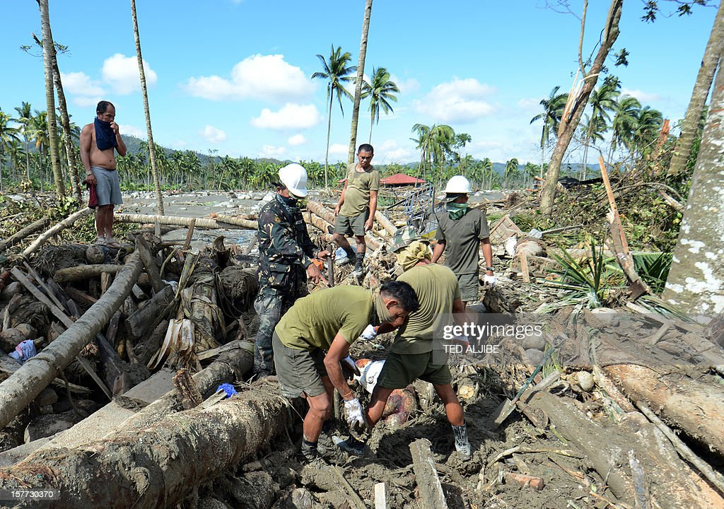 Philippine military personnel dig through debris as they retrieve a victim's body in the town of New Bataan, compostela province on December 6, 2012. Nearly 200,000 people are homeless and more than 300 dead after the Philippines suffered its worst typhoon this year, authorities said on December 6, reaching out for international aid to cope with the scale of the disaster.
