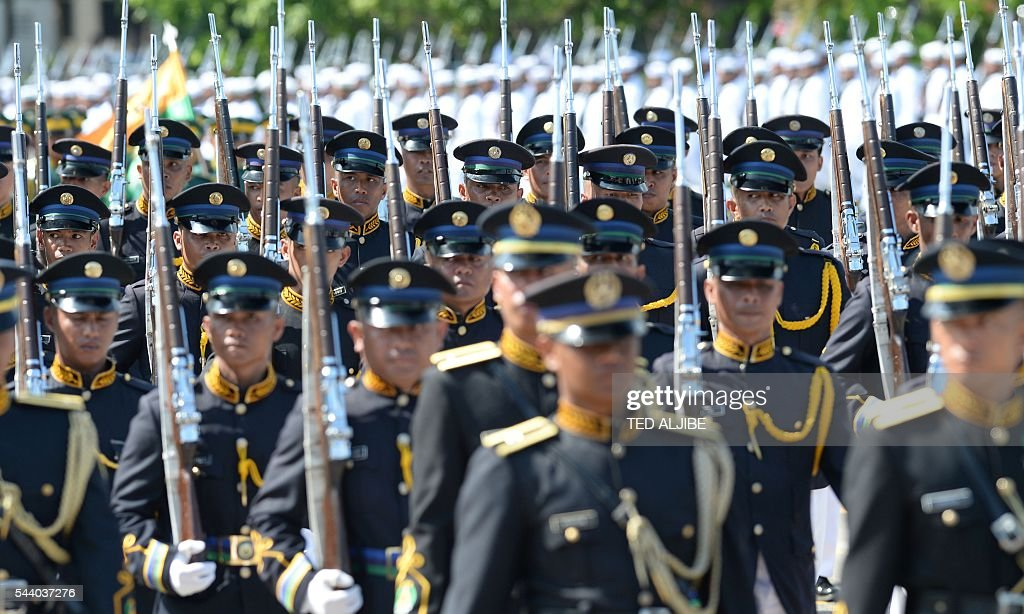 Philippine military personnel march during a parade in honour of President Rodrigo Duterte at the military headquarters in Manila on July 1, 2016. Duterte was sworn in as the Philippines' president June 30 -- and quickly launched a foul-mouthed vow to wipe out drug traffickers and even urged ordinary Filipinos to kill addicts. / AFP / TED