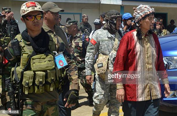 Philippine Muslim rebel leader Nur Misuari of the Moro National Liberation Front is escorted by his bodyguards as he arrives at the airport in Jolo...