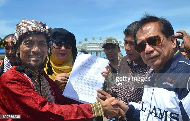 Philippine Muslim rebel leader Nur Misuari of the Moro National Liberation Front shake hands with presidential peace adviser Jesus Dureza at the...