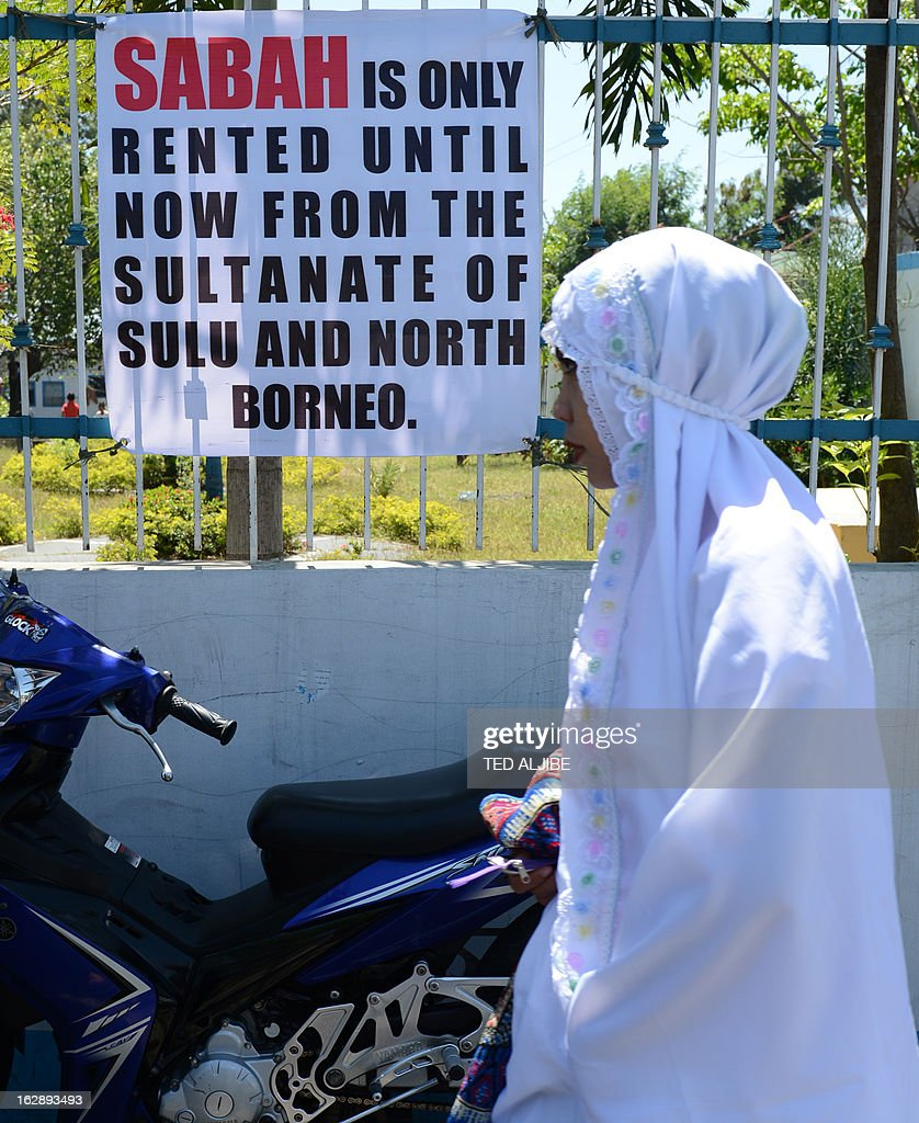 A Philippine Muslim woman walk past a placard on the Sabah stand-off over a territorial dispute, after attending Friday prayers at a mosque in Manila on March 1, 2012, where Malaysian authorities ended the Sabah stand-off with Filipino gunmen. Philippines says 3 dead, 10 arrested in Malaysia Sabah stand-off. AFP PHOTO/TED ALJIBE