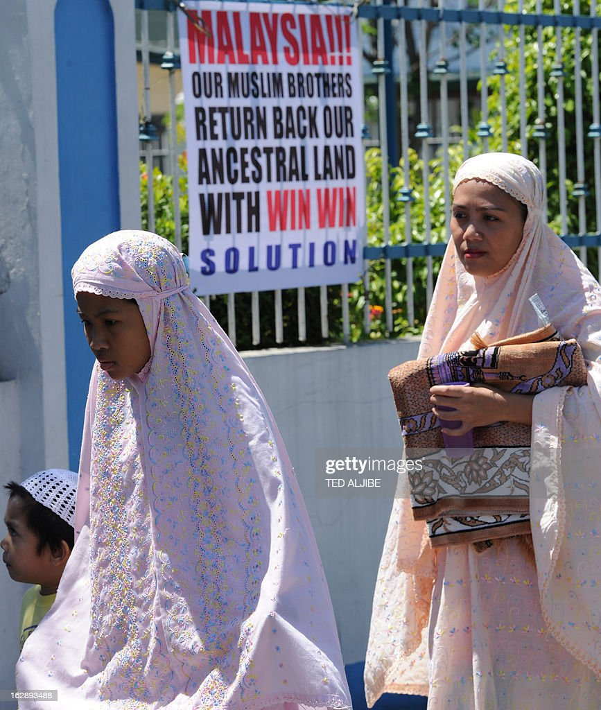 Philippine Muslims walk past a placard on the Sabah stand-off during after attending Friday prayers at a mosque in Manila on March 1, 2012, where Malaysian authorities ended the Sabah stand-off with Filipino gunmen. Philippines says 3 dead, 10 arrested in Malaysia Sabah stand-off.