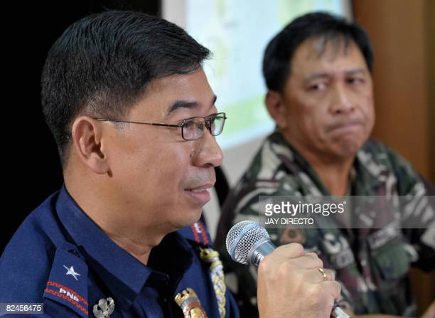 Philippine National Police spokesman Chief Superintendent Nicanor Bartolome is watched by his military counterpart Brigadier General Jorge Segovia as...