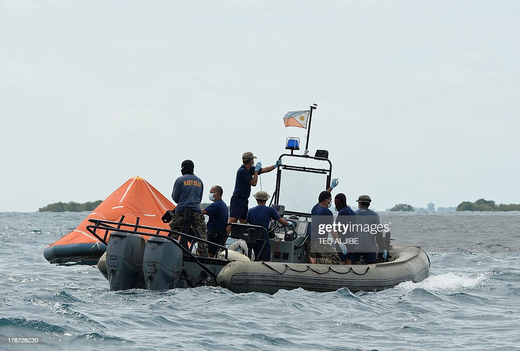 Philippine navy personnel continue a search operation next to a floating life raft at the site of a ferry collision in Talisay near Cebu City, central Philippines on August 18, 2013. Philippine rescuers struggled in rough seas on August 18 as they resumed a bleak search for 85 people missing in the country's latest ferry disaster, but insisted miracle survivor stories were possible.