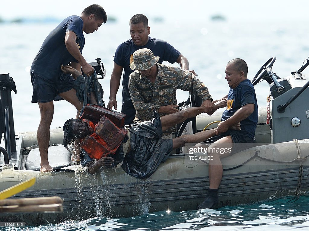 Philippine Navy personnel lift a victim from the sea during rescue operations on August 17, 2013 after a cargo ship collided with the ferry St. Thomas Aquinas the night before off the town of Talisay near the Philippines' second largest city of Cebu. Stormy weather forced Philippine rescuers to suspend a search on August 17 for 171 people missing after a crowded ferry collided with a cargo ship and quickly sank, with 31 others confirmed dead.