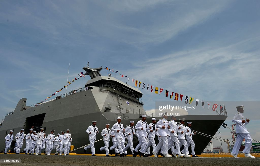 Philippine Navy personnel march in front of the newly-commissioned BRP Tarlac (LD-601), an amphibious landing dock vessel, during the Philippine Navy's 118th anniversary celebrations at Pier 13, South Harbor, in Manila on June 1, 2016. The 118th anniversary of the Philippine Navy was celebrated with the simultaneous commissioning of the BRP Tarlac, the newest ship in the navy's inventory. / AFP / NOEL