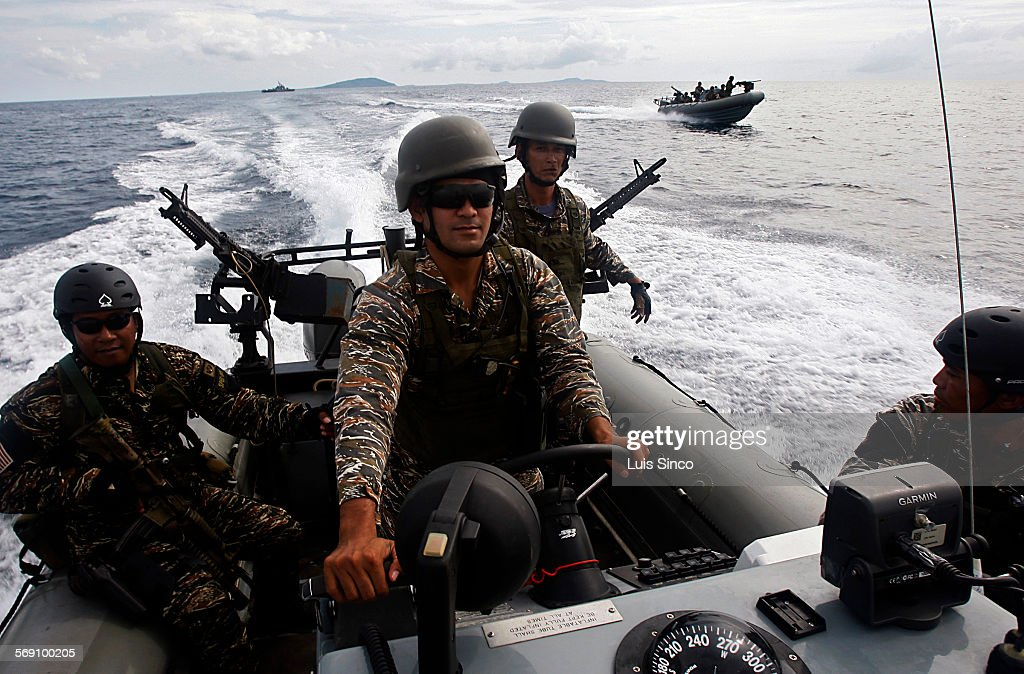 CITY PHILIPPINES – JULY 21 2009 Philippine Navy SEALS aboard inflatable watercraft patrol the waters near Basilan Island a hotbed of Muslim...