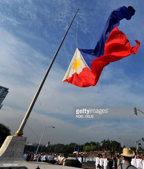 Philippine outgoing President Gloria Macapagal Arroyo holds the rope during the flag raising ceremony on its 112th anniversary of the proclamation of...