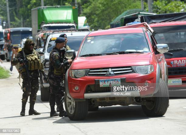 Philippine police check a car fleeing from Marawi where gunmen who had declared allegiance to the Islamic State group rampaged through the southern...