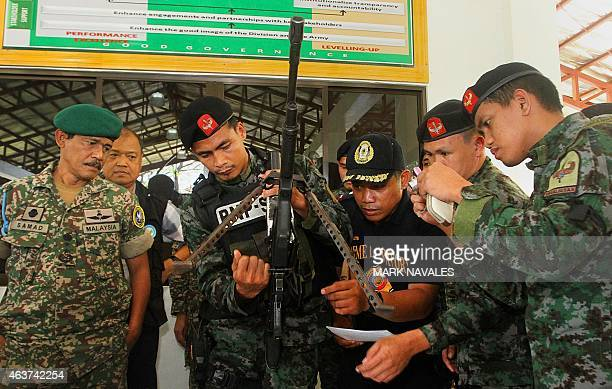 Philippine police commandos and officers along with an international peace monitoring team inspect high powered firearms at a military camp in...