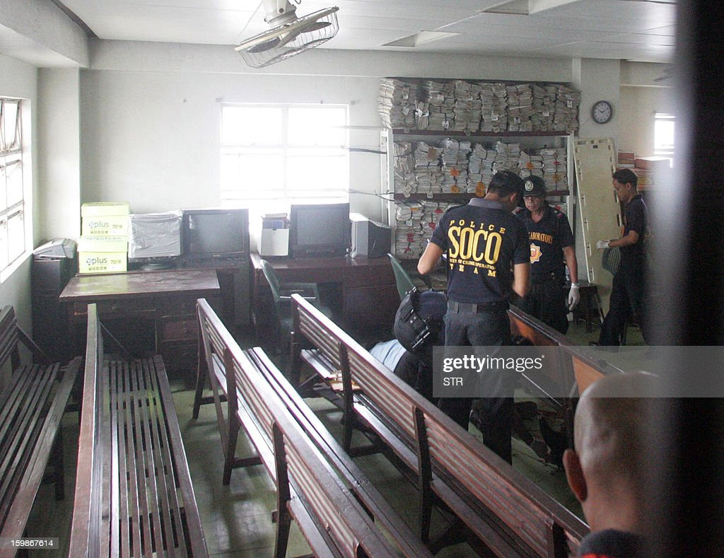 Philippine police investigators collect evidence inside a court room in Cebu City, central Philippines on January 22, 2013, where a Canadian national shot dead two people. A Canadian man shot dead two people including a lawyer in a Philippines courtroom on January 22, using a pistol he smuggled inside the court as he went on trial for petty mischief, police said. AFP PHOTO