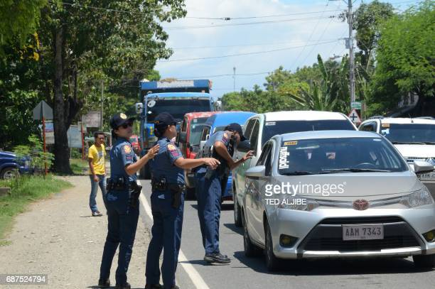 A Philippine police officers man a checkpoint along a highway in Iligan City in southern island of Mindanao on May 24 2017 Philippine President...