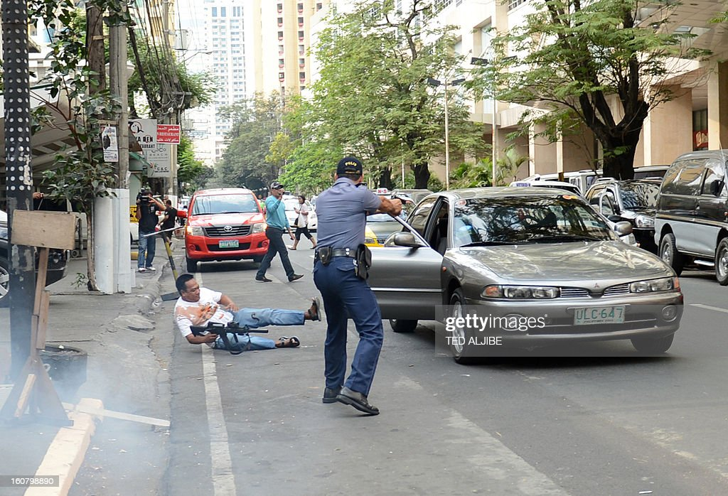 A Philippine policeman (R) aims his gun at a man acting as a robber (L) during a shopping mall robbery simulation in Manila on February 6, 2013, as part of heightened security and police visibility after recent attacks at shopping centres. Police have stepped up their visibility and security in response to recent attacks in popular Manila shopping malls, including the ransacking of a mall jewellery store on January 26.