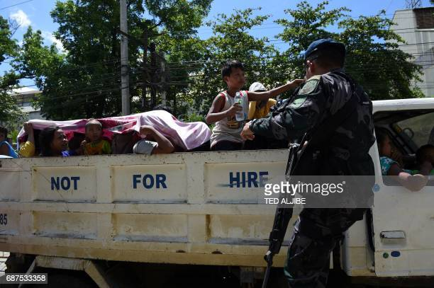 A Philippine policeman checks evacuees from Marawi aboard a truck at a checkpoint by the entrance of Iligan City in southern island of Mindanao on...