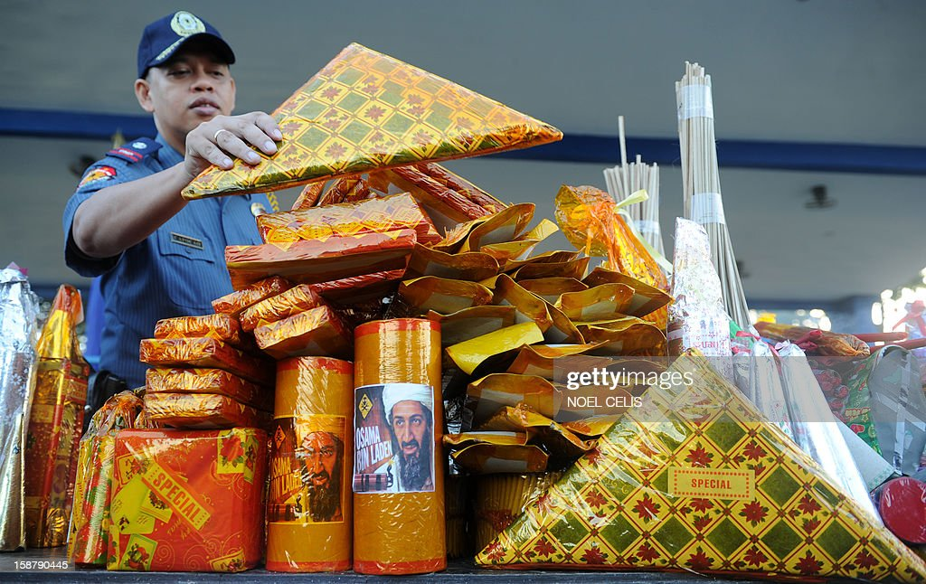 A Philippine policeman displays confiscated firecrackers, including one (bottom C) called 'Bin Laden,' in an effort to minimize the use illegal pyrotechnics ahead of the coming New Year festivities, at police headquarters in Manila on December 29, 2012. The Philippines is mainly Roman Catholic, but New Year's celebrations draw on ancient superstitions and Chinese traditions in which the noise from firecrackers is meant to drive away evil spirits and bring good luck in the coming year. Adding to the danger of annual fireworks celebrations in the streets, there are over 1.2 million unlicensed firearms in the Philippines and some of those are used in the festivities. AFP PHOTO / NOEL CELIS