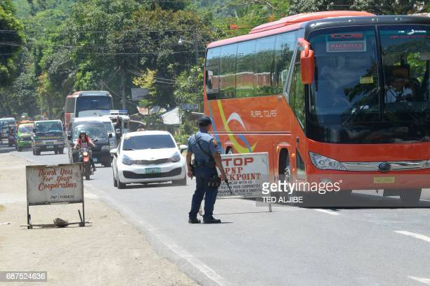A Philippine policeman mans a checkpoint along a highway in Iligan City in southern island of Mindanao on May 24 2017 Philippine President Rodrigo...