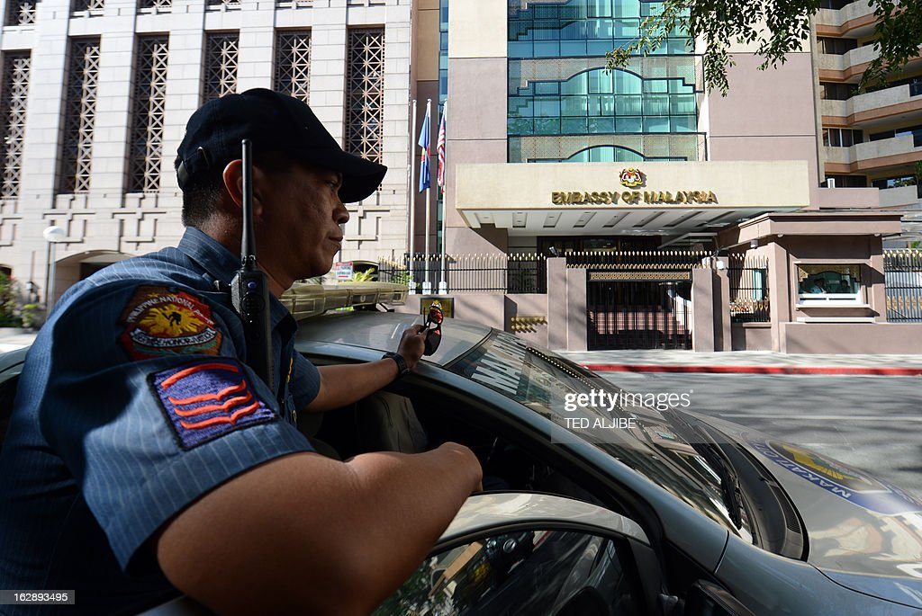 A Philippine policeman stands guard near the Malaysian embassy in the financial district of Manila on March 1, 2013, after authorities heigthened security around the embassy premises after Malaysian authorities ended the Sabah stand-off with Filipino gunmen. Philippines says 3 dead, 10 arrested in Malaysia Sabah stand-off.