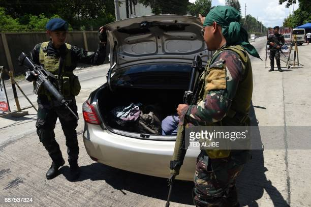 Philippine policemen check a car boot of a resident fleeing from Marawi city where gunmen who had declared allegiance to the Islamic State group...