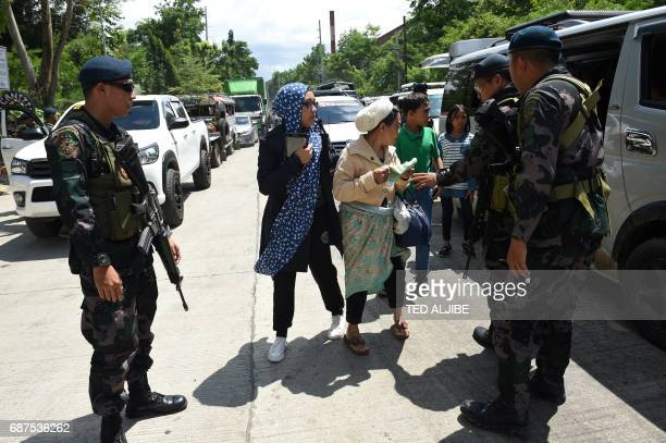 Philippine policemen check evacuees from Marawi aboard a van at a checkpoint by the entrance of Iligan City in southern island of Mindanao on May 24...