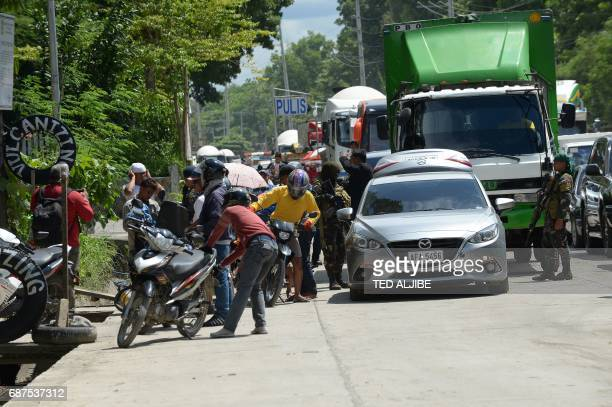 Philippine policemen check the belongings of residents fleeing Marawi city where gunmen who had declared allegiance to the Islamic State group...