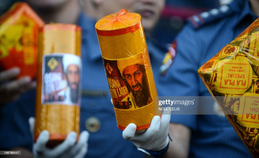 Philippine policemen shows confiscated firecrackers, including one (C) called 'Bin Laden,' in an effort to minimize the use illegal pyrotechnics ahead of the coming New Year festivities, at police headquarters in Manila on December 29, 2012. The Philippines is mainly Roman Catholic, but New Year's celebrations draw on ancient superstitions and Chinese traditions in which the noise from firecrackers is meant to drive away evil spirits and bring good luck in the coming year. Adding to the danger of annual fireworks celebrations in the streets, there are over 1.2 million unlicensed firearms in the Philippines and some of those are used in the festivities.