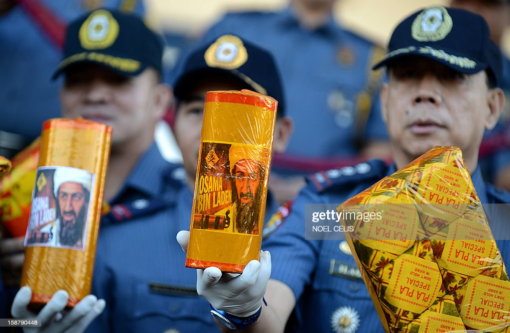 Philippine policemen shows confiscated firecrackers, including one (C) called 'Bin Laden,' in an effort to minimize the use illegal pyrotechnics ahead of the coming New Year festivities, at police headquarters in Manila on December 29, 2012. The Philippines is mainly Roman Catholic, but New Year's celebrations draw on ancient superstitions and Chinese traditions in which the noise from firecrackers is meant to drive away evil spirits and bring good luck in the coming year. Adding to the danger of annual fireworks celebrations in the streets, there are over 1.2 million unlicensed firearms in the Philippines and some of those are used in the festivities. AFP PHOTO / NOEL CELIS