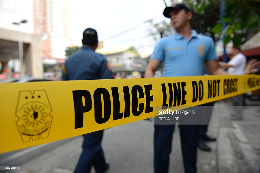 Philippine policemen stand next to a police cordon line during a simulation of a mall robbery in Manila on February 6, 2013, as part of heightened security after recent attacks at shopping centres. Police have stepped up their visibility and security in response to recent attacks in popular Manila shopping malls, including the ransacking of a mall jewellery store on January 26. AFP PHOTO/TED ALJIBE