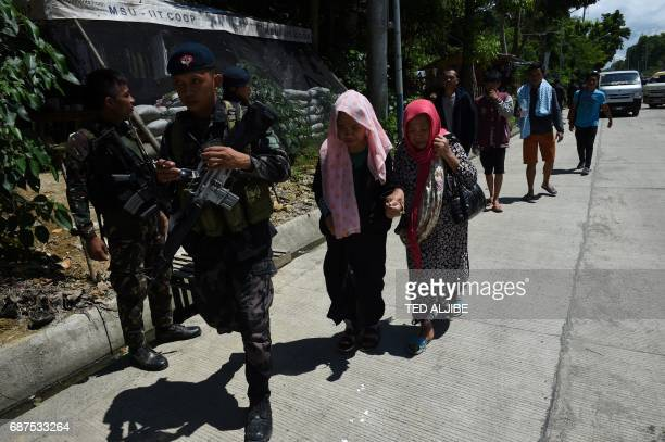 Philippine policemen walk with evacuees from Marawi at a checkppoint by the entrance of Iligan City in southern island of Mindanao on May 24 2017...