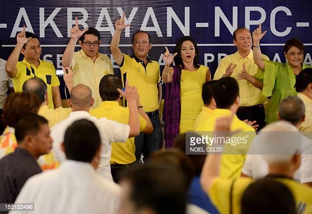 Philippine President Benigno Aquino gestures the 'Laban' sign with the administration's senatorial lineup for the 2013 polls Congressman Edgardo...