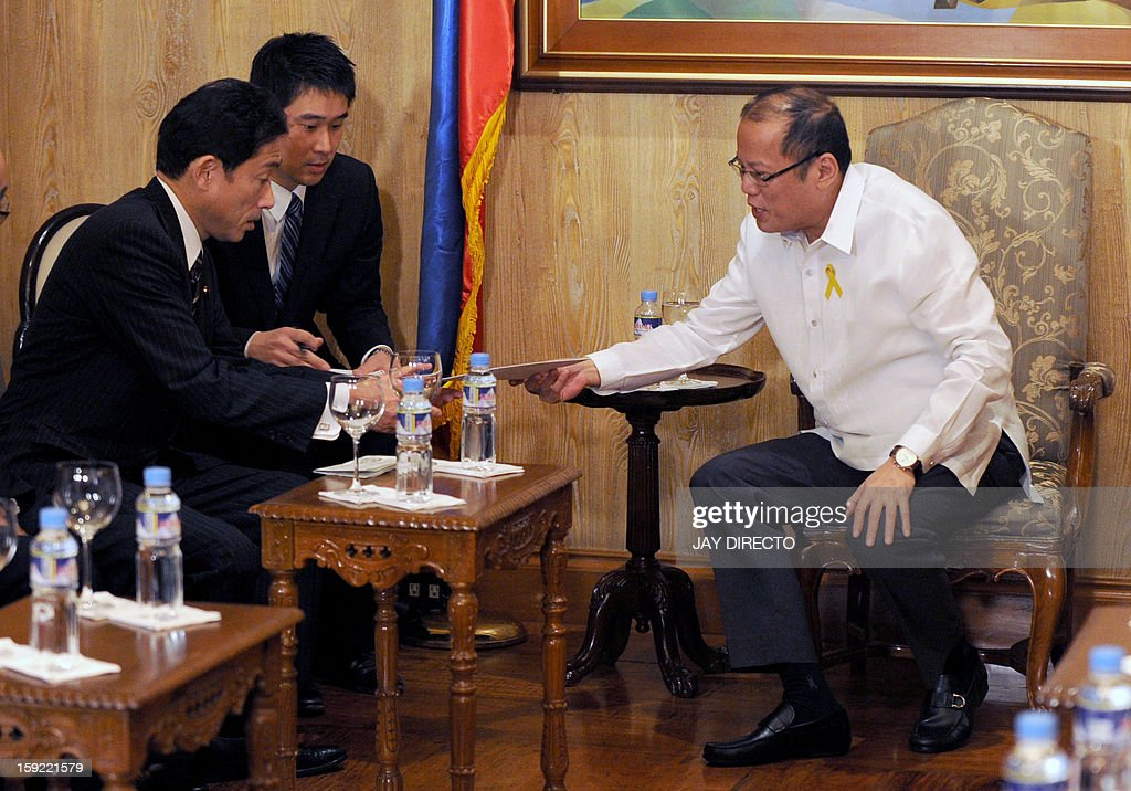 Philippine President Benigno Aquino (R) hands over a document to Japanese Foreign Minister Fumio Kishida (L) during his courtesy call in Malacanang Palace in Manila on January 10, 2013. Japanese Foreign Minister Fumio Kishida called on January 10 for stronger ties with the Philippines to help ensure regional peace, amid tense territorial disputes by both countries with a rising China. AFP PHOTO / Jay DIRECTO