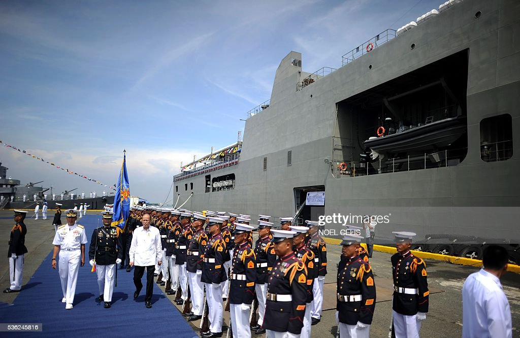 Philippine President Benigno Aquino (4th L) inspects honour guards standing in formation beside the newly-commissioned BRP Tarlac (LD-601), an amphibious landing dock vessel, during the Philippine Navy's 118th anniversary celebrations at Pier 13, South Harbor, in Manila on June 1, 2016. The 118th anniversary of the Philippine Navy was celebrated with the simultaneous commissioning of the BRP Tarlac, the newest ship in the navy's inventory. / AFP / NOEL