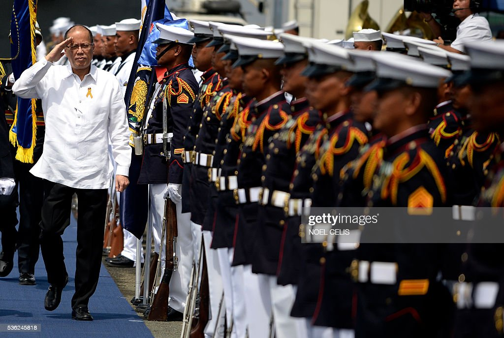 Philippine President Benigno Aquino (L) inspects honour guards standing in formation beside the newly-commissioned BRP Tarlac (LD-601), an amphibious landing dock vessel, during the Philippine Navy's 118th anniversary celebrations at Pier 13, South Harbor, in Manila on June 1, 2016. The 118th anniversary of the Philippine Navy was celebrated with the simultaneous commissioning of the BRP Tarlac, the newest ship in the navy's inventory. / AFP / NOEL