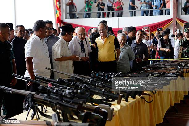 Philippine President Benigno Aquino looks on weapons surrendered by the country's largest Muslim rebel the Moro Islamic Liberation Front during the...
