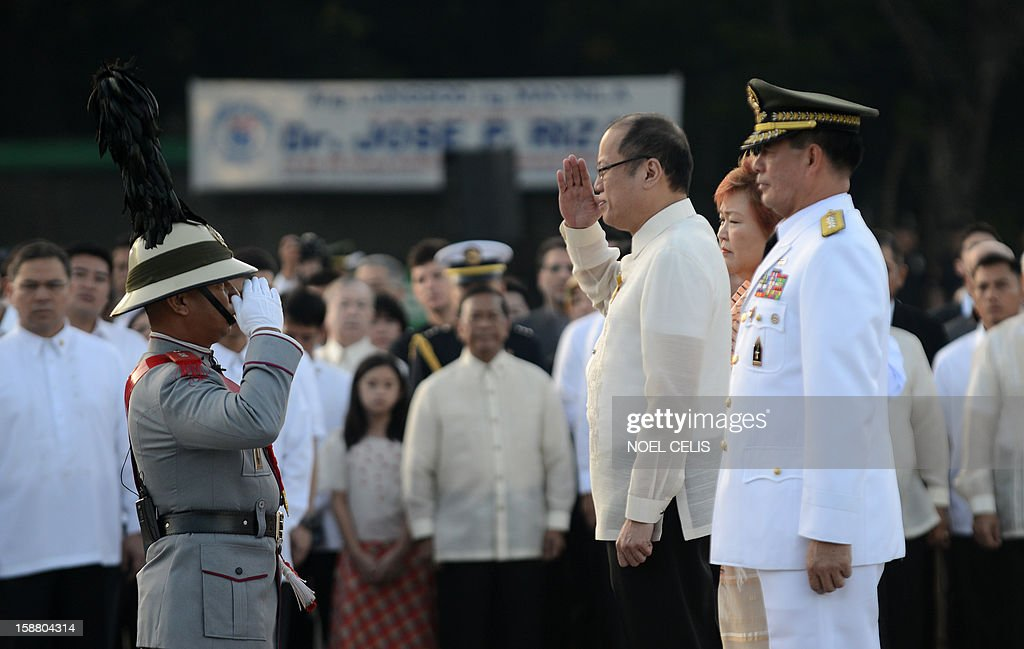 Philippine President Benigno Aquino (C) salutes an honour guard during a wreath-laying ceremony on the 106th anniversary of Philippine national hero Jose Rizal at the Luneta Park in Manila on December 30, 2012. Rizal was sentenced to death by a firing squad of the Spanish army after he was accused of leading a revolution against Spain.