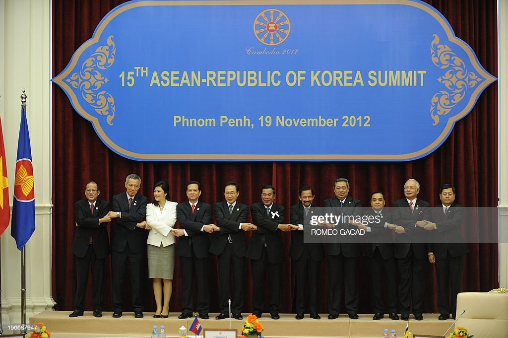 Philippine President Benigno Aquino, Singapore Prime Minister Lee Hsien Loong, Thai Prime Minister Yingluck Shinawatra, Vietnamese Prime Minister Nguyen Tan Dung, South Korean President Lee Myung Bak , Cambodian Prime Minister Hun Sen, Brunei Sultan Hassanal Bolkiah, Indonesian President Susilo Bambang Yudhoyono, Laos Prime Minister Thongsing Thammavong, Malaysian Prime Minister Najib Razak and Myanmar Deputy Foreign Minister Kan Zaw join hands together for a family photo session during the Association of Southeast Asian Nations (ASEAN) and Korea summit in Phnom Penh on November 19, 2012 following the 21st ASEAN Leaders Summit.
