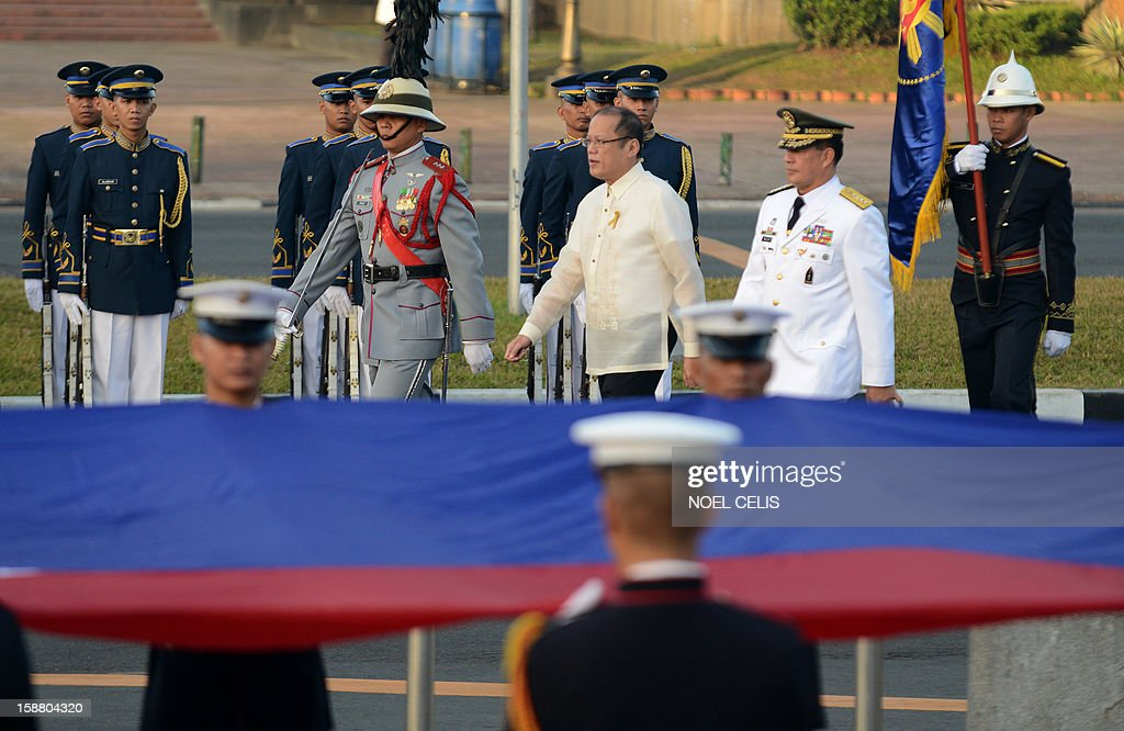 Philippine President Benigno Aquino (C) walks past honour guards during a wreath-laying ceremony on the 106th anniversary of Philippine national hero Jose Rizal at the Luneta Park in Manila on December 30, 2012. Rizal was sentenced to death by a firing squad of the Spanish army after he was accused of leading a revolution against Spain. AFP PHOTO / NOEL CELIS