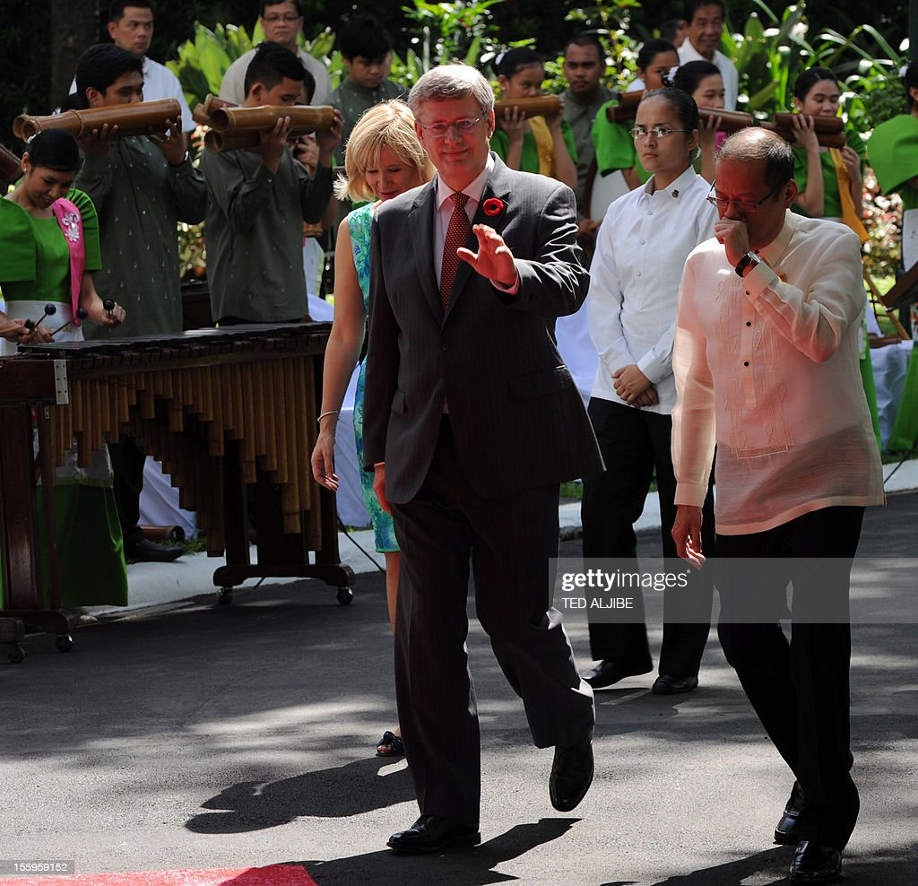 Philippine President Benigno Aquino (R) walks with Canadian Prime Minister Stephen Harper (L) and his wife Laureen (back, L) as they walk past members of a bamboo orchestra during the welcoming ceremony for the prime Minister and his party at Malacanang Palace in Manila on November 10, 2012. Harper is in the Philippines for a two-day official visit.