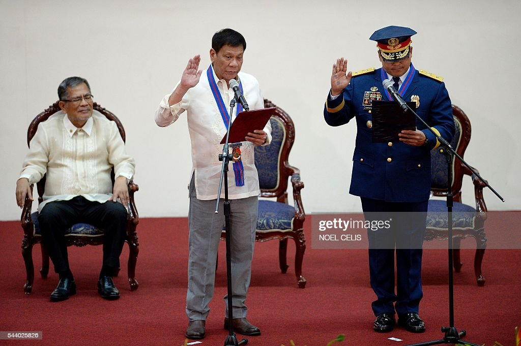 Philippine President Rodrigo Duterte (C) administers the oath taking of Philippine National Police (PNP) chief Ronald Bato Dela Rosa during Dela Rosa's Assumption of Command Ceremony at the Camp Crame in Manila on July 1, 2016. Authoritarian firebrand Rodrigo Duterte was sworn in as the Philippines' president on June 30, after promising a ruthless and deeply controversial war on crime would be the main focus of his six-year term. / AFP / NOEL