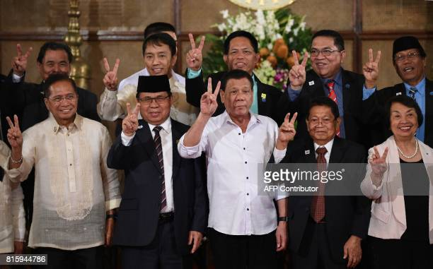 Philippine President Rodrigo Duterte along with members of government and Moro Islamic Liberation Front peace representatives gestures with the peace...