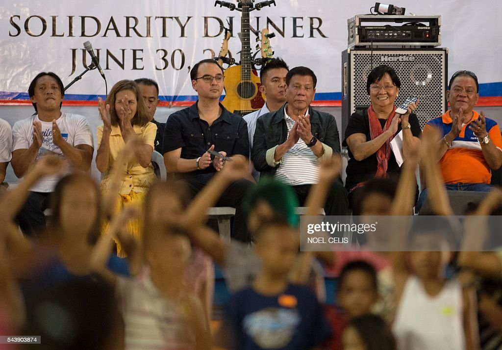Philippine President Rodrigo Duterte claps as children belonging to poor families perform a dance as he visited families living in slum area of Manila on June 30, 2016. Authoritarian firebrand Rodrigo Duterte was sworn in as the Philippines' president on June 30, after promising a ruthless and deeply controversial war on crime would be the main focus of his six-year term. / AFP / NOEL