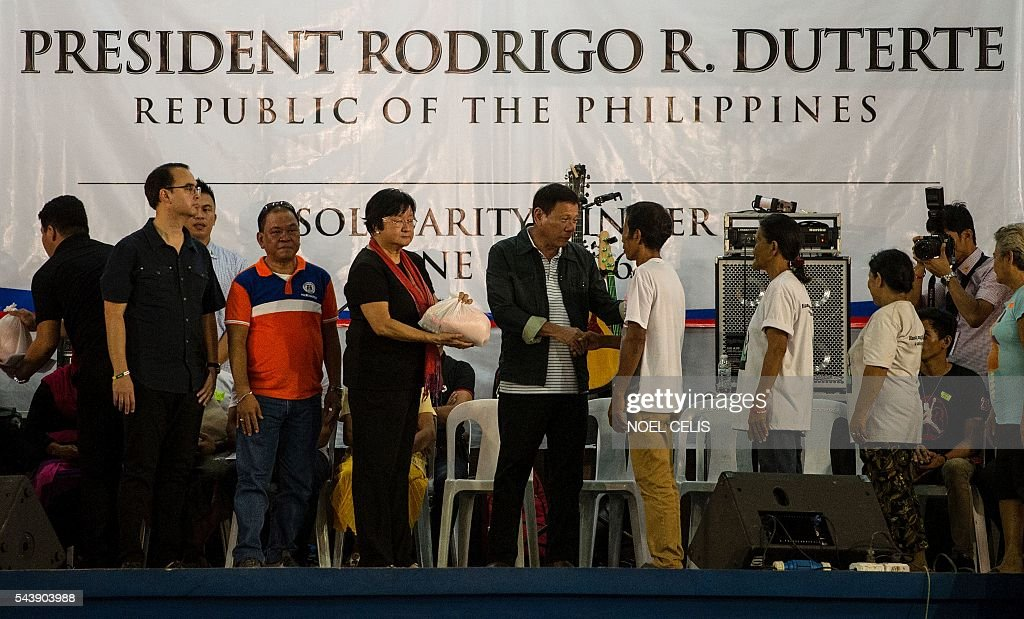 Philippine President Rodrigo Duterte distributes food packs to poor families as he visited families living in slum area of Manila on June 30, 2016. Authoritarian firebrand Rodrigo Duterte was sworn in as the Philippines' president on June 30, after promising a ruthless and deeply controversial war on crime would be the main focus of his six-year term. / AFP / NOEL