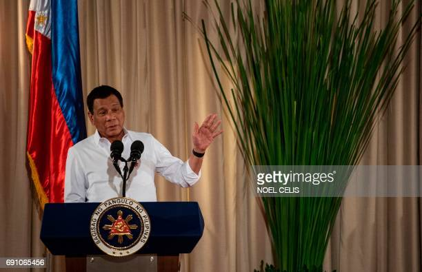 Philippine President Rodrigo Duterte gestures as he gives a speech during the mass oath taking of officials of various national leagues at the...