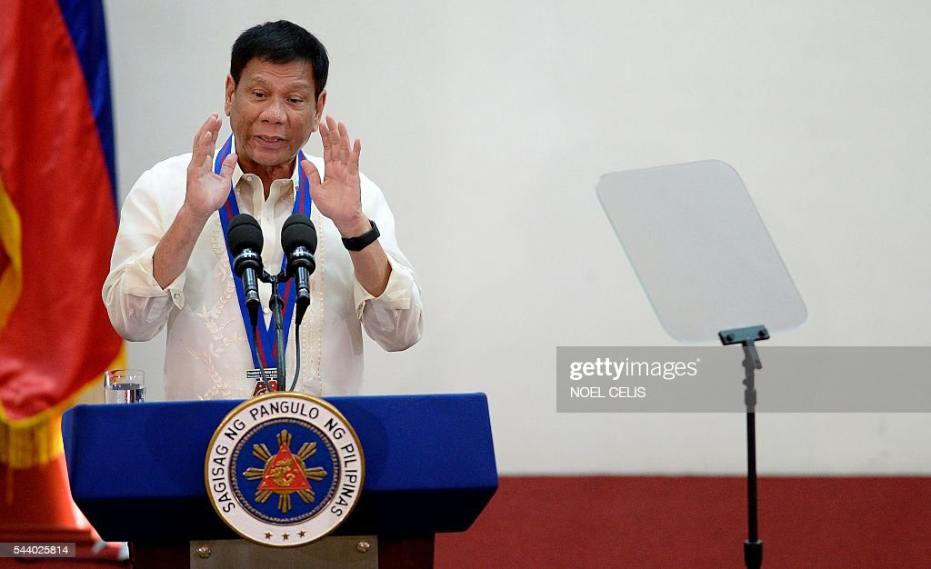 Philippine President Rodrigo Duterte gestures as he talks during the Assumption of Command Ceremony of Philippine National Police (PNP) chief Ronald Bato Dela Rosa at the Camp Crame in Manila on July 1, 2016. Authoritarian firebrand Rodrigo Duterte was sworn in as the Philippines' president on June 30, after promising a ruthless and deeply controversial war on crime would be the main focus of his six-year term. / AFP / NOEL