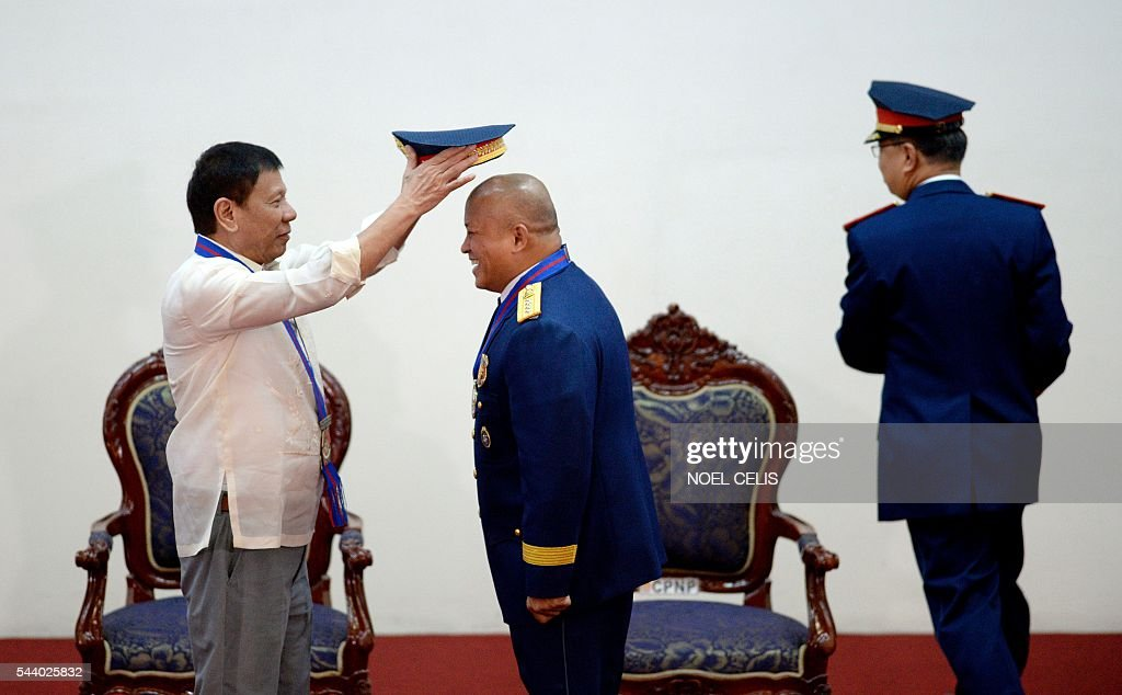 Philippine President Rodrigo Duterte gestures puts a hat on Philippine National Police (PNP) chief Ronald Bato Dela Rosa during Dela Rosa's Assumption of Command Ceremony at the Camp Crame in Manila on July 1, 2016. Authoritarian firebrand Rodrigo Duterte was sworn in as the Philippines' president on June 30, after promising a ruthless and deeply controversial war on crime would be the main focus of his six-year term. / AFP / NOEL